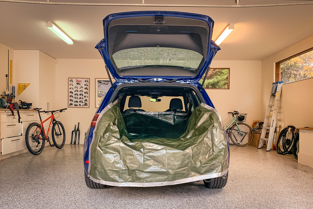 Garage containing blue hatchback with hatch open and olive-green tarp inside