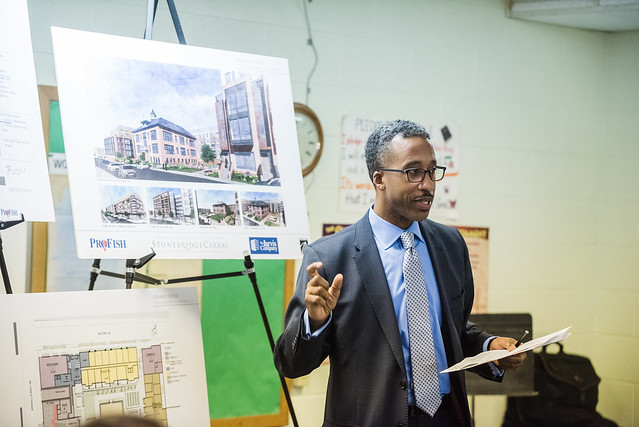 Photo of Councilmember McDuffie holding some notes, smiling, and gesticulating in front of several printed display boards.