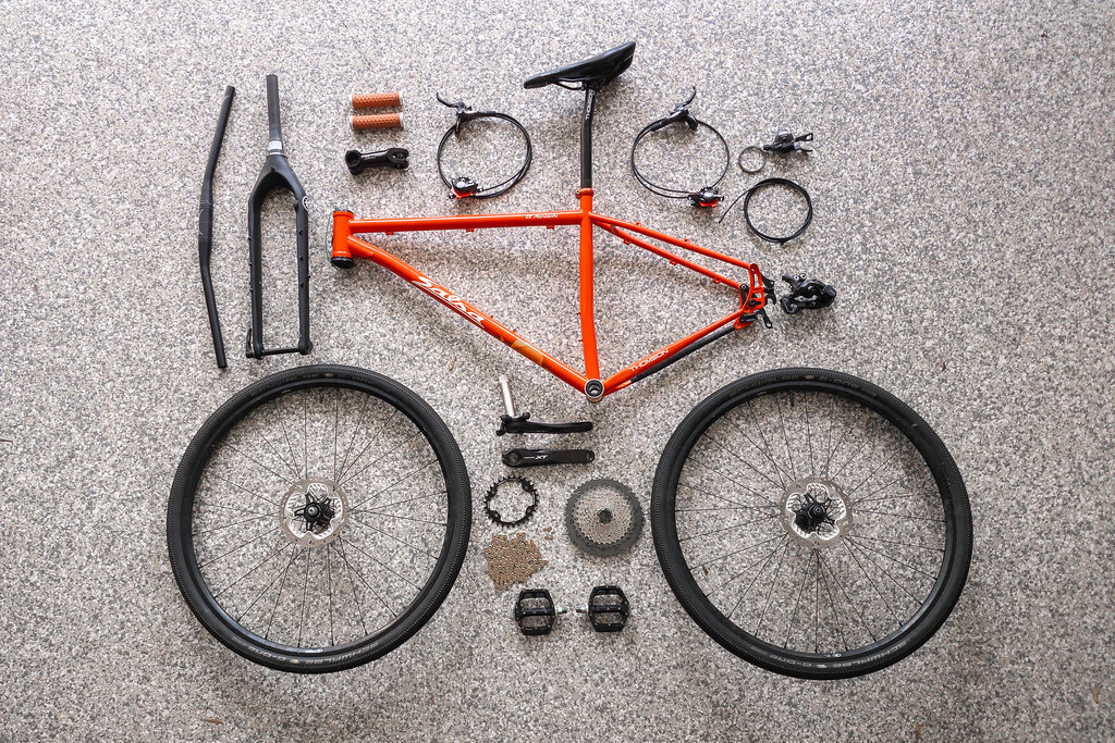 All parts for a mountain bike laid out on a garage floor