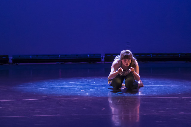 A dancer kneels on stage during a performace in the Dancing Community production.