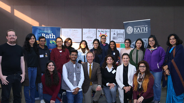Group of students and academic staff pose in front of University of Bath banners