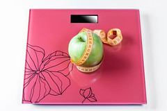 Apple wrapped with measuring tape on the scales as a symbol of a healthy diet