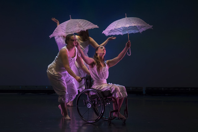 Three dancers perform on stage with umbrellas.