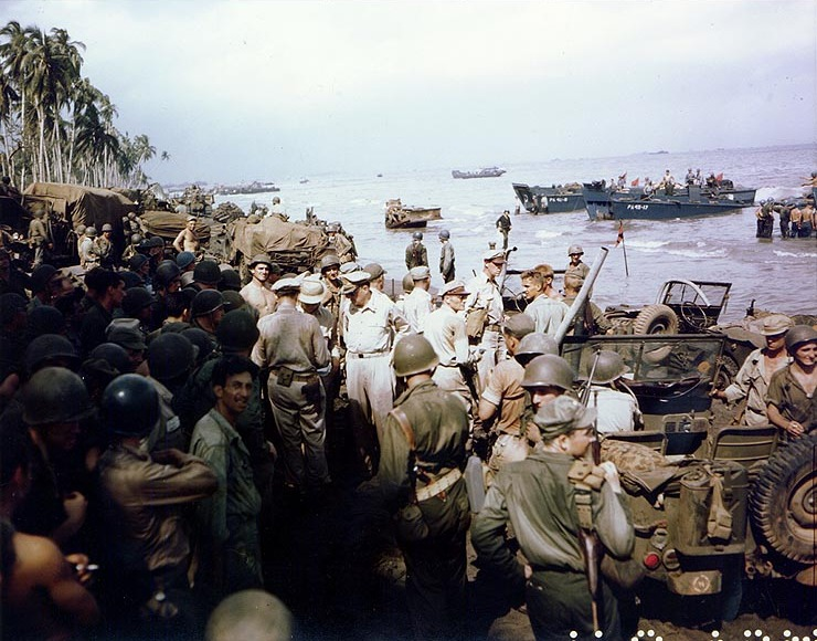 General Douglas MacArthur (center), accompanied by Lieutenant Generals George C. Kenney and Richard K. Sutherland and Major General Verne D. Mudge (Commanding General, First Cavalry Division), inspecting the beachhead on Leyte Island on October 20, 1944, with a crowd of onlookers.