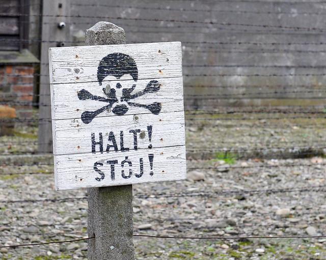 Cartel de Halt Stoj en alemán junto a las alambradas nazis