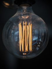 Close-up shot of glowing filaments in an incandescent light bulb
