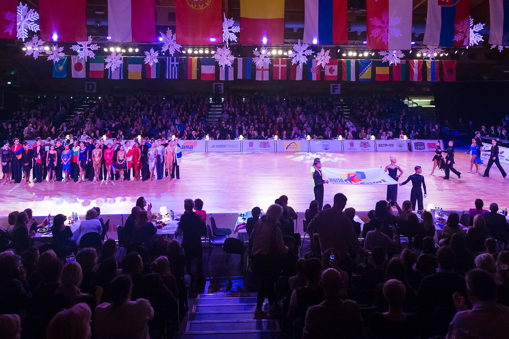 Riga, Latvia-December 15, 2018: Professional Adult Dance Couples Posing Together on Dancefloor With WDSF Flag Demonstration on WDSF Baltic Grand Prix-2108 Championship in December 15, 2018 in Riga