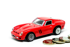 Red toy car with coins on white background