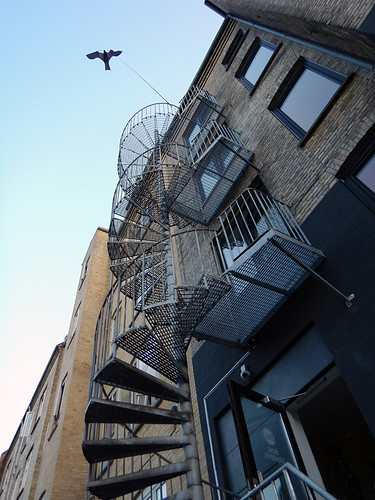 A wrought-iron spiral staircase on the outside of a building in Aalborg, Denmark