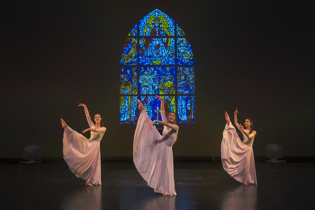 Three dancers perform on stage in front of a stained glass window during a production of Dancing Community.