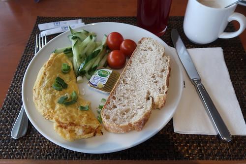 Für mich zubereitetes Omelett mit Pilzen und Käse zu aufgeschnittenen Gurken, Minitomaten und Weißbrot mit Butter