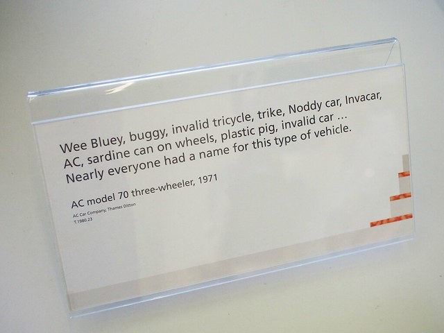 "Gallery placard: ""Wee Bluey, buggy, invalid tricycle, trike, Noddy car, Invacar, AC, sardine can on wheels, plastic pig, invalid car ... Nearly everyonoe had a name for this type of vehicle. AC model 70 three-weeler, 1971"""