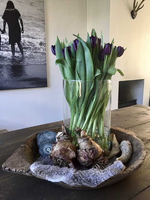 Vaas met tulpen in houten schaal op salontafel