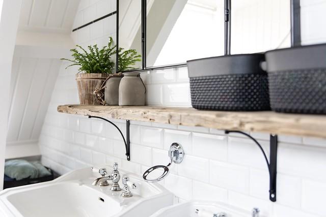 Houten plank boven wastafels met mandjes