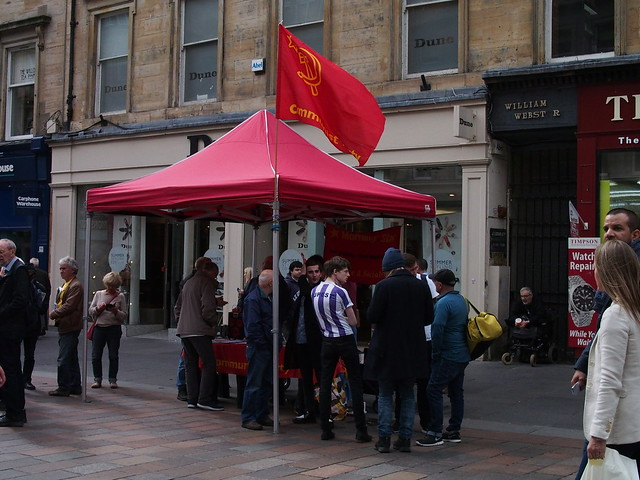 a red marquee with a communist party flag in city pedestrian mall with lots of people around