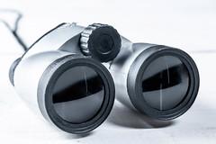 Gray binoculars close-up on white background