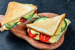 Two sandwiches with ham, cheese, tomatoes, lettuce, and toasted bread. Top view