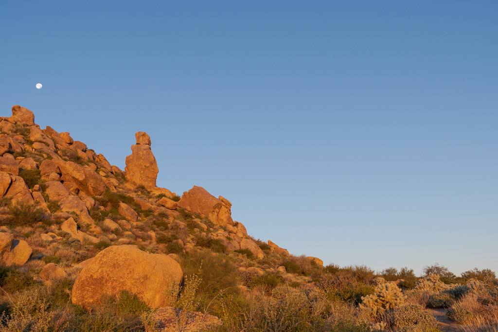 A rock formation resembling a smiling face looks out over the desert at sunrise on the Marcus Landslide Trail in McDowell Sonoran Preserve