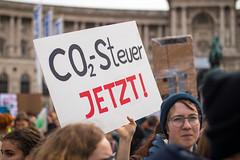 Demonstrantin mit einem CO2-Steuer Jetzt! Transparent. Demo gegen Umweltverschmutzung und Klimaerwärmung