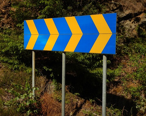 In Sweden the dangerous curve signs are yellow and blue like the Swedish flag