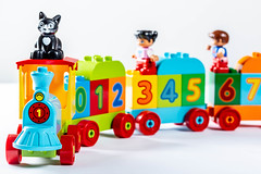 Toy train with wagons carries kids and cat