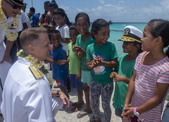 Rear Adm. Joey Tynch lets a Marshallese child try on his cover at the Eniburr pier during Pacific Partnership. (U.S. Navy/MC3 Chanel Turner)