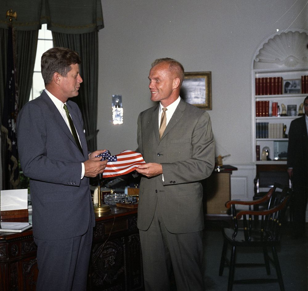 KN-C22489 President John F. Kennedy receives a gift of an American flag from astronaut Lieutenant Colonel John H. Glenn, Jr. (right); Lt. Col. Glenn carried the flag in his space suit during his orbital flight aboard Mercury-Atlas 6, also known as Friendship 7. Special Assistant to the President, Kenneth P. O'Donnell, stands partially out of frame in the background. Oval Office, White House, Washington, D.C. Photo taken on June 27, 1962.