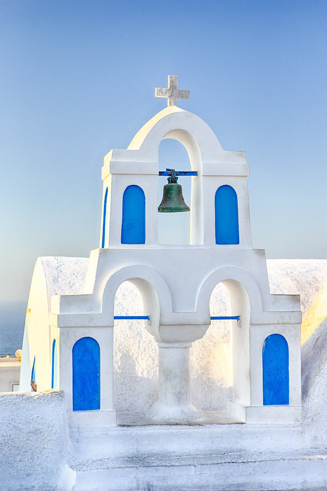 Famous European Destinations. Classic White Roofed Chirch with Blue Inserts and Bell on Oia Village in Santorini Island in Greece