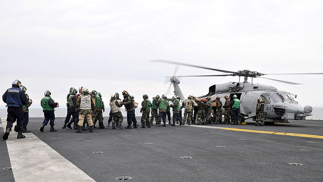 Sailors and Marines aboard an aircraft for humanitarian assistance
