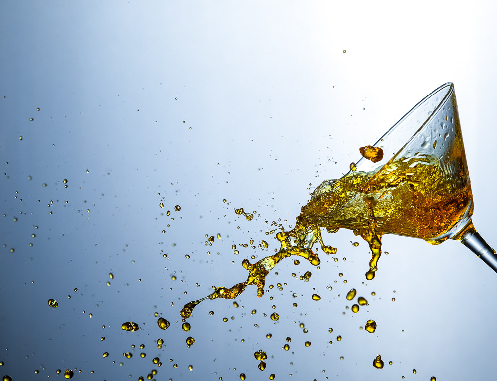 Liquids Photography. Colofur Drink Droplets Poured Out of The Clear Wine Glass.