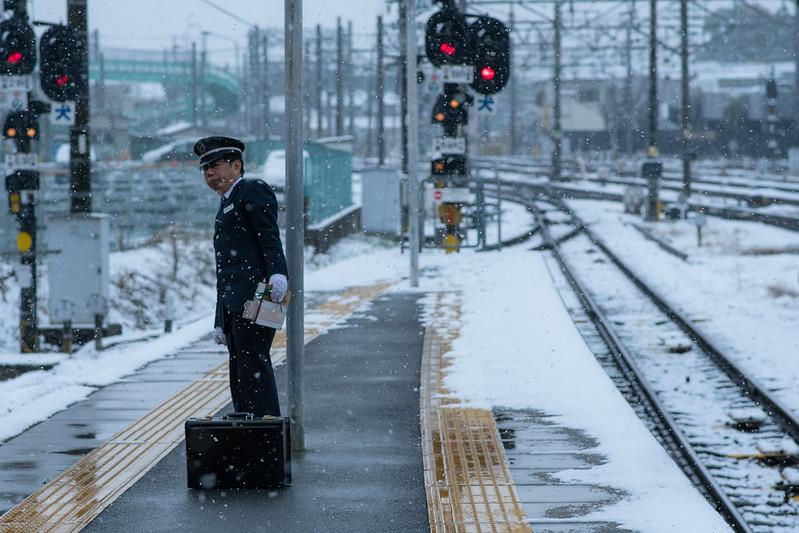 雪が降る名鉄線のホームと駅員さんの写真