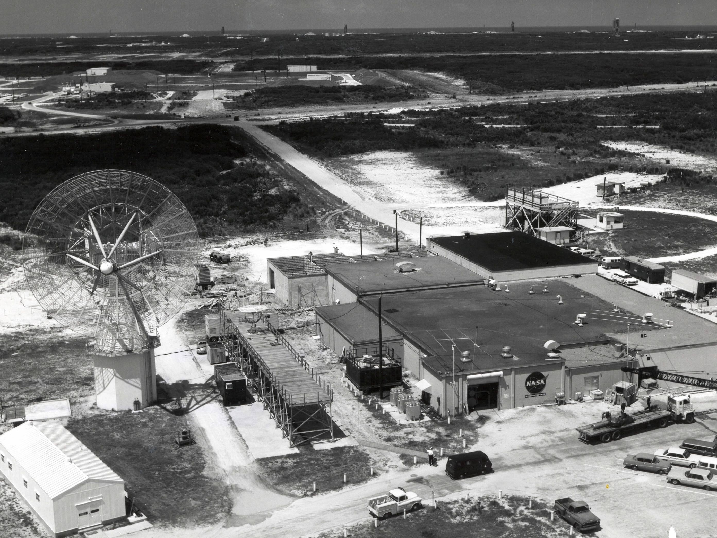 Mercury Control Center at Cape Canaveral with Missile Row in the background. Between 1962 and 1963, the facility was modified to handle the additional complexities of the Gemini Program. In 1962, Pan American World Airways Inc. was contracted to design an addition to the facility, which wrapped around the east, north, and most of the west and south sides. This addition included areas for flight control briefing, data analysis, and a large space for a new Gemini spacecraft trainer. Photo taken on June 4, 1963.