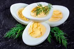 Boiled chicken eggs with dill sprigs on black stone