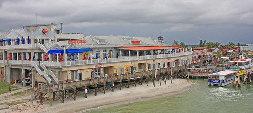 bubbagumpshrimpcompany bubbagumpshrimpco madeirabeach florida fl pinellascounty unitedstates usa us america gulfboulevard gulfblvd johnspassinlet johnspassboardwalk touristarea touristtrap tourists touristexcursions beachgoers recreationarea shops restaurants beaches waterfront waterway saltwater water intercostalwaterway intercoastalwaterway brownpelicans sand sandbar barrierisland umbrellas thatchumbrellas palmtrees gulfofmexico gulfcoast gulf people