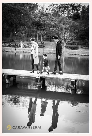 公園の池のそばで散策する親子 モノクロ写真