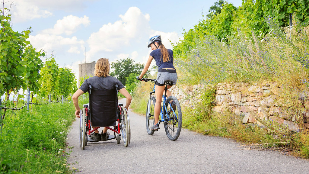 A man in a wheel chair next to a woman on a bicycle on a sunny footpath