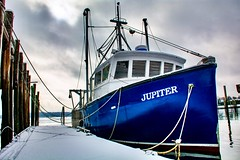 Bright blue fishing boat tied up at the dock.