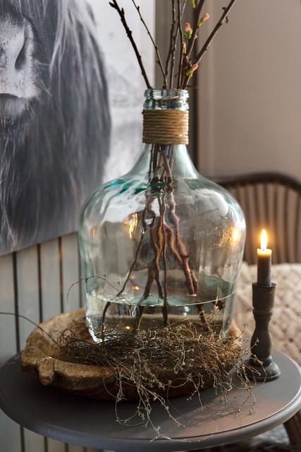 Glazen fles met takken stoer wonen
