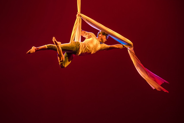 A performer in the air with an aerial hammock during a production of Dancing Community.