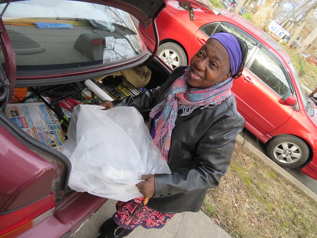 Photo of a woman pulling a large bag-covered tray out of the trunk of a car.