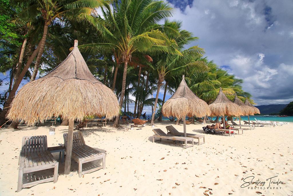 native-style huts and hammocks on the beach at Inaladelan Island Resort