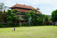 The twins hold hands as they run across the huge soccer field in downtown Ubud