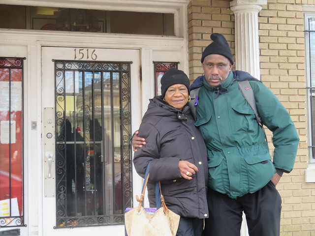 Photo of a woman and a man in heavy winter coats standing on a porch with one arm around each other.