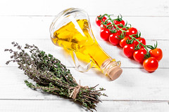 Cherry tomatoes branch, fresh thyme with olive oil on white wooden background