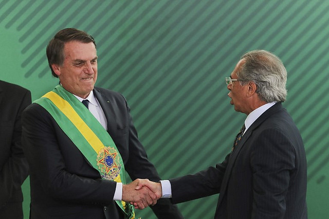 Brazilian president Jair Bolsonaro (right) shakes hands with his economy minister and author of pension reform draft proposal, Paulo Guedes - Créditos: Sergio Lima/AFP