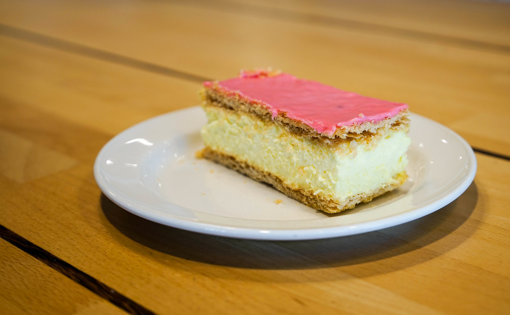 Picture of a roze cake, which is pink on top, with cream sitting inside two wafers