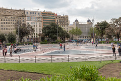 Placa de Catalunya with pigeons and people on star-shaped pattern of red-blue floor tiles in Barcelona, Spain