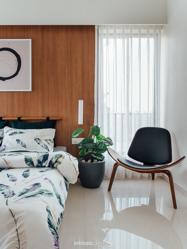 Small modern bedroom with artwork and leather chair