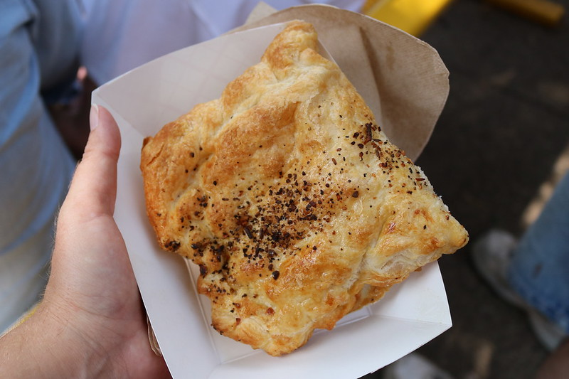 A hand holding a paper tray with a square pastry with a stripe of dark spices in the middle.