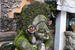 Smiling statue with flowers in Ubud
